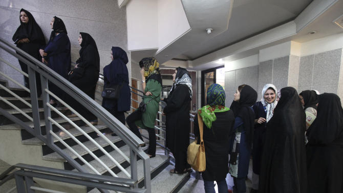 Iranian women queue in a polling station to vote for the presidential and municipal councils elections, in Tehran, Iran, Friday, June 14, 2013. Iran's supreme leader delivered a salty rebuke to the U.S. Friday as Iranians lined up to vote in a presidential election that has suddenly become a showdown across the Islamic Republic's political divide: hard-liners looking to cement their control and re-energized reformists backing the lone moderate. (AP Photo/Vahid Salemi)
