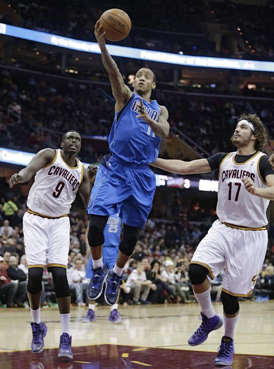 Dallas Mavericks' Monta Ellis (11) shoots between Cleveland Cavaliers' Loul Deng, (9) from Sudan, and Cleveland Cavaliers' Anderson Varejao (17), from Brazil, during the first quarter of a