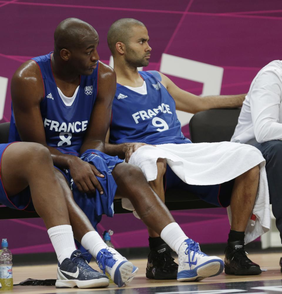 France's Ali Traore and Tony Parker watch from the bench during the second half of a preliminary men's basketball game against Team USA at the 2012 Summer Olympics, Sunday, July 29, 2012, in London. (AP Photo/Charles Krupa)