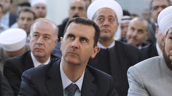 FILE - In this Sunday, Aug. 19, 2012 file photo released by the Syrian official news agency SANA, Syrian president, Bashar Assad, performs Eid prayers in the Hamad Mosque in Damascus, Syria. With even his most powerful ally, Russia, losing faith in him, President Bashar Assad may appear to be heading for a last stand against rebel forces who have been waging a ferocious battle to overthrow him for nearly two years. But Assad still has thousands of elite and loyal troops behind him, and analysts say that even if he wanted to give up the fight, it's unclear those around him would let him abandon ship and leave them to an uncertain fate. (AP Photo/SANA, File)