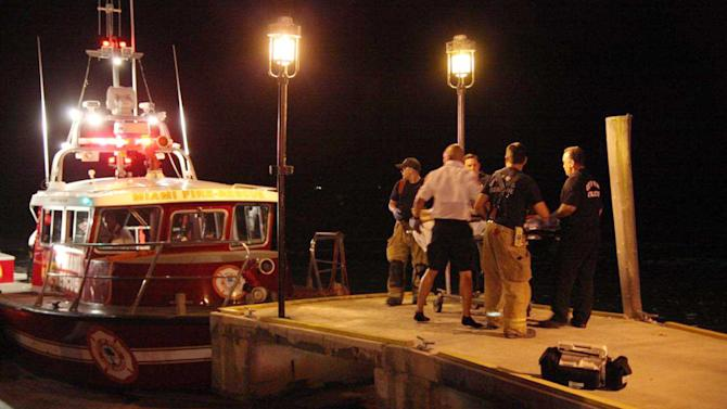 Emergency workers carry an injured person on a stretcher on Friday night, July 4, 2014 after three boats collided near a Miami marina around the end of a fireworks display. Four were killed and a dozen others injured. (AP Photo/Miami Fire Rescue, Lt. Ignatius Carroll Jr.)