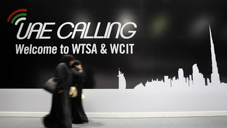Emirati women pass by a billboard on the final day of World Conference on International Telecommunications in Dubai, United Arab Emirates, Friday, Dec. 14, 2012. Envoys in Dubai signed a new U.N. telecommunications treaty Friday that a U.S.-led delegation says endorses greater government control of the Internet. The U.S. and more than 20 other countries refused to ratify the accord by the 193-nation International Telecommunications Union.(AP Photo/Kamran Jebreili)