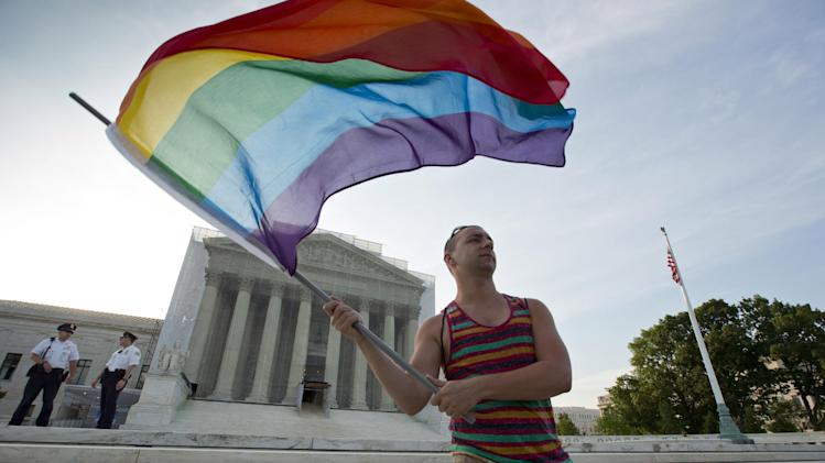 FILE- In this June 26, 2013 file photo, gay rights advocate Vin Testa waves a rainbow flag in front of the Supreme Court in Washington. On June 26, 2013, the U.S. Supreme Court issued a pair of landmark rulings, one striking down a law that denied federal recognition to same-sex marriages and the other clearing the way for gay couples to wed legally in California. In the 12 months since the Supreme Court issued a pair of landmark rulings on same-sex marriage, the ripple effects of those rulings have transformed the national debate over marriage, prompting many people on both sides to conclude that its spread nationwide is inevitable. (AP Photo/J. Scott Applewhite, File)