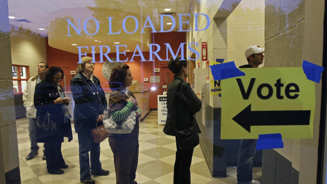 Behind a sign barring loaded firearms in the building, people stand in line to cast their votes on Election Day as the polls opened at a precinct at the Wake County Firearms Education and Training Center in Apex, N.C., Tuesday, Nov. 6, 2012. (AP Photo/Gerry Broome)