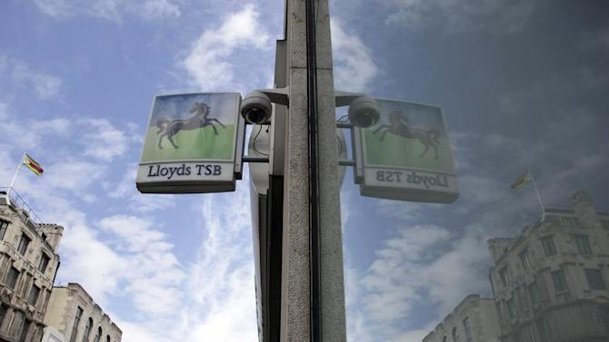 A sign from a branch of a Lloyds bank is reflected in a window in central London