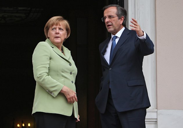 Greece&#39;s Prime Minister Antonis Samaras, right, and Germany&#39;s Chancellor Angela Merkel speak before their meeting at the Maximos mansion in Athens, Tuesday, Oct. 9, 2012. Amid draconian security measures and a mass protest, German Chancellor Angela Merkel arrived Tuesday for her first visit to Greece since the eurozone crisis began there three years ago. Her five-hour stop is seen by the Greek government as a historic boost for the country&#39;s future in Europe, but by protesters as a harbinger of more austerity and hardship. (AP Photo/Thanassis Stavrakis, Pool)