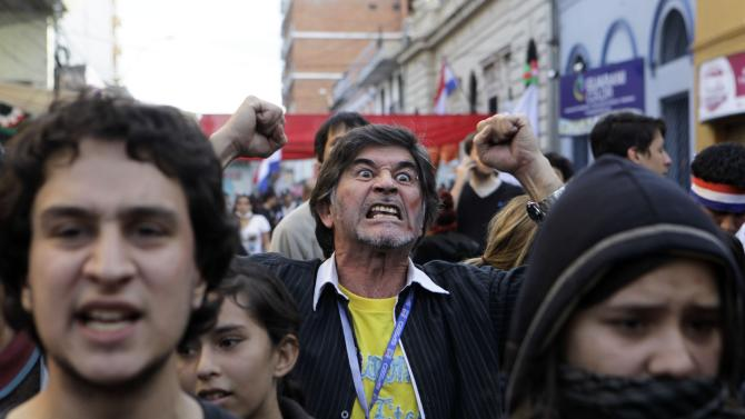 People protest against Paraguay's new President Federico Franco outside a public TV station in Asuncion, Paraguay, Sunday, June 24, 2012. Paraguay's new government battled a wave of criticism on Sunday as several of the nation's closest allies condemned the dismissal of President Fernando Lugo by lawmakers, some calling it a congressional coup. (AP Photo/Jorge Saenz)