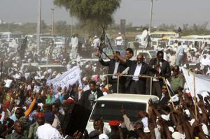 Sudanese President and NCP candidate Omar Hassan al-Bashir waves to supporters at start of election campaign ahead of 2015 presidential elections in Madani