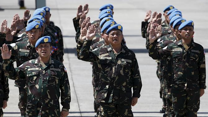 Armed Forces of the Philippines personnel deploying to the United Nations peacekeeping mission in Haiti, take their oaths during a sending-off ceremony at the Villamor air base in Pasay city