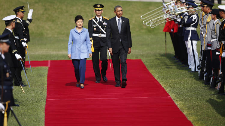 U.S. President Barack Obama, center right, and South Korean President Park Geun-hye, center left, inspect an honor guard during a welcome ceremony at the Presidential Blue House in Seoul, Friday, April 25, 2014. (AP Photo/Kim Hong-Ji, Pool)