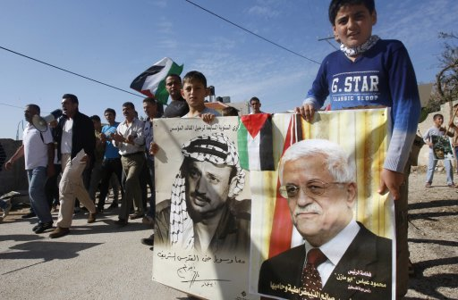Palestinian boys hold a placard depicting Palestinian President Abbas and the late Palestinian leader Arafat during a demonstration marking the anniversary of Arafat's death, near Nablus
