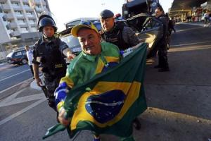 A soccer fan holds a Brazilian flag in front of two policemen outside Ana Rosa subway station during the fifth day of metro worker's protest in Sao Paulo