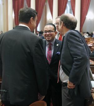 Assemblyman Luis Alejo, D-Watsonville, smiles as he talks with Sen. Joel Anderson, R-Alpine,left, and Mark Wyland, R-Escondido, as the Senate voted on Alejo's minimum wage bill at the Capitol in Sacramento, Calif., Thursday, Sept. 12, 2013. The Senate approved Alejo's bill to raise the minimum wage from the current $8 an hour to $10 by 2016. Both Anderson and Wyland voted against the bill.(AP Photo/Rich Pedroncelli)
