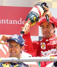 Spain's Ferrari driver Fernando Alonso, right, sprays champagne over Germany's second placed Red Bull driver Sebastian Vettel after winning the German F1 Grand Prix in Hockenheim, Germany,  Sunday, July 22, 2012. (AP Photo/Michael Probst)