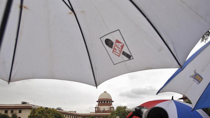 A television journalist reports news from the premises of the Supreme Court as it rains in New Delhi