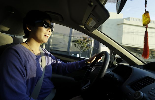 In this Jan. 4, 2013 photo, Lyft driver Nancy Tcheou smiles as she drives in San Francisco. Fed up with traditional taxis, city dwellers are tapping their smartphones to hitch rides from strangers using mobile apps that allow riders and drivers to find each other. Internet-enabled ridesharing services such as Lyft, Uber and Sidecar are expanding rapidly in San Francisco, New York and other U.S. cities, billing themselves as a high-tech, low-cost alternative to cabs. (AP Photo/Jeff Chiu)