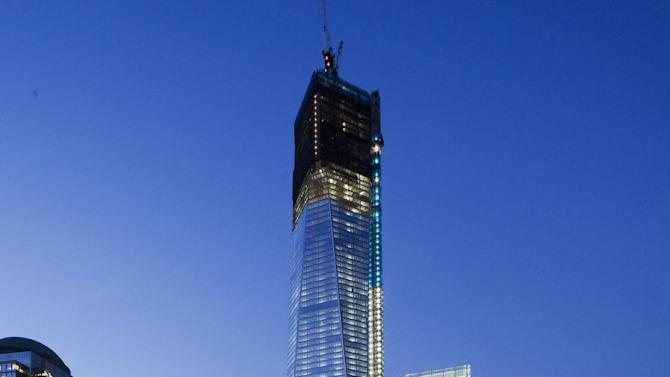 FILE - In this Sept. 5, 2012 file photo, One World Trade Center rises above the square outlines of the National September 11 Memorial in New York. (AP Photo/Mark Lennihan, File)