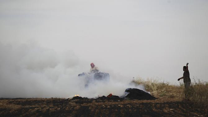 A man gestures towards civil defense members as he stands near burning farmland targeted by what activists said were airstrikes by forces loyal to Syria's President Bashar al-Assad in Maarshmarin village in Idlib countryside