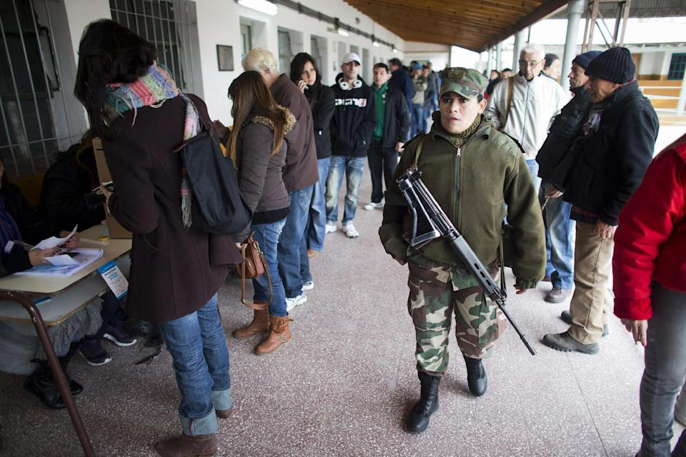 An Argentine soldier provides security at a voting station in Buenos Aires' Tigre district , Argentina, Sunday, Aug. 11, 2013. Argentines went to the polls in a nationwide mandatory primaries to select candidates for the Oct. 27 midterm election for legislators and senators.(AP Photo/Victor R. Caivano)