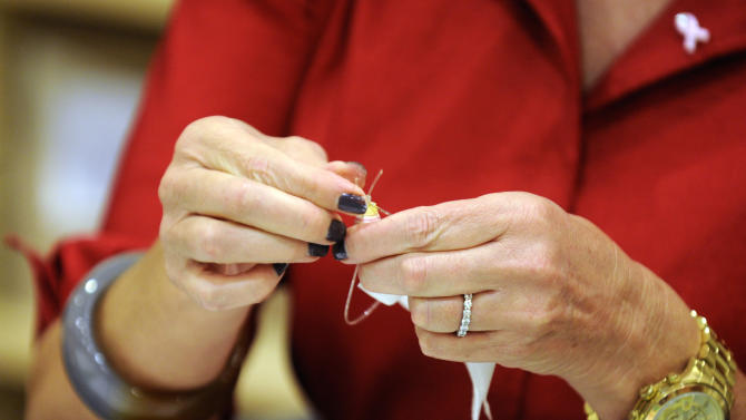 Ann Romney, wife of Republican presidential candidate, former Massachusetts Gov. Mitt Romney, makes a bracelet with cancer survivors during a tour of the Center for Women's Oncology at Moffitt Cancer Center Wednesday, Oct. 10, 2012 in Tampa, Fla. (AP Photo/The Tampa Tribune, Chris Urso, Pool)
