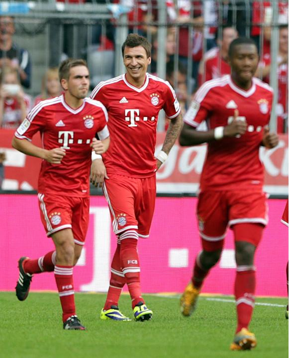 Bayern's Mario Mandzukic of Croatia, center, smiles after scoring his side's first goal  during the German first division Bundesliga soccer match between FC Bayern Munich and Hertha BSC Berlin, in Mun