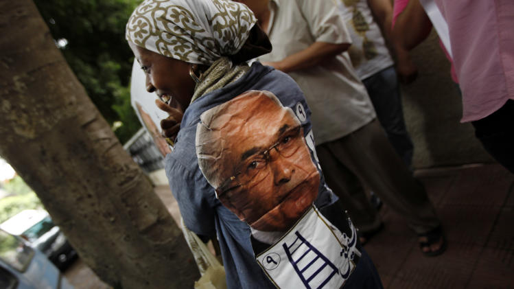 "An Egyptian woman wears a poster of presidential candidate Ahmed Shafiq on her shirt during a press conference at Shafiq's office in Cairo, Egypt, Saturday, May 26, 2012. Egyptian presidential candidate Ahmed Shafiq paid tribute Saturday to the ""glorious revolution"" that toppled Hosni Mubarak, a dramatic turn-around for the former regime official who fought his way into the runoff elections by appealing to public disenchantment with last year's uprising. (AP Photo/Khalil Hamra)"