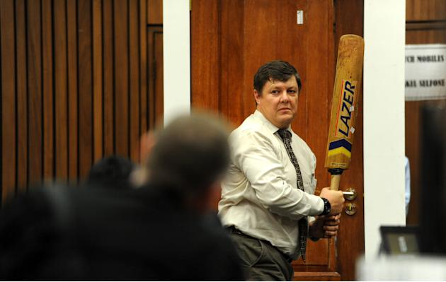 Forensic investigator Johannes Vermeulen, with a cricket bat in hand, demonstrates on a mock-up toilet cubicle, with the door, background, how the door could have been broken down with the bat, during