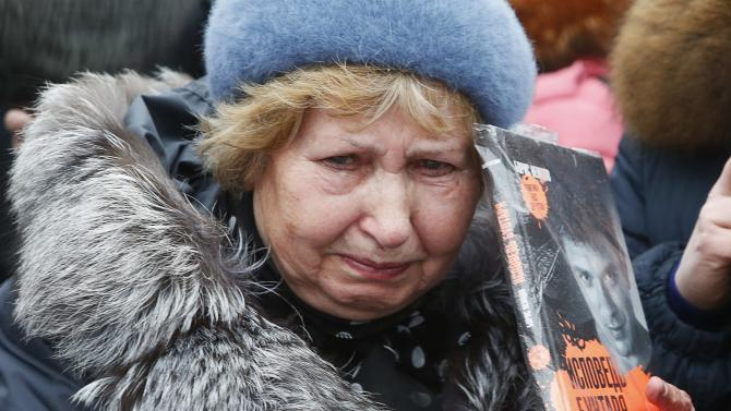 A woman reacts as she visits the site, where Boris Nemtsov was recently murdered, in central Moscow