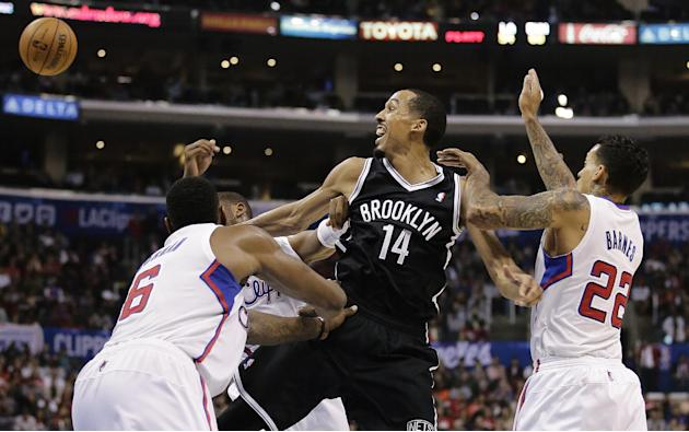 Brooklyn Nets' Shaun Livingston, center, passes the ball as he is defended by Los Angeles Clippers' DeAndre Jordan, left, and Matt Barnes during the second half of an NBA basketball game on Saturday,