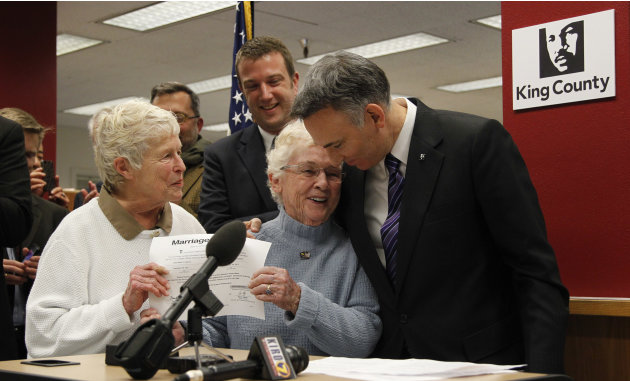 King County Executive Dow Constantine, right, leans down to embrace Pete-e Petersen as her partner, Jane Abbott Lighty, watches after Constantine issued them the first marriage license to a same-sex c