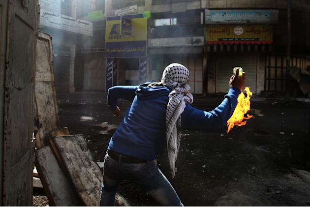 A Palestinian protester throws a Molotov cocktail towards Israeli soldiers, not pictured, during clashes in the West Bank city of Hebron, Wednesday, April 3, 2013. Palestinian prisoners have been riot