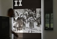 A man walks past an old photograph of deportation of Jews in World War II during an exhibition in the Central Office for the Investigation of National Socialist Crimes in Ludwigsburg, southwestern Germany, on September 3, 2013. The office said Tuesday it would send files on 30 former Auschwitz death camp personnel to state prosecutors with a recommendation to bring charges. (AFP Photo/Thomas Kienzle)