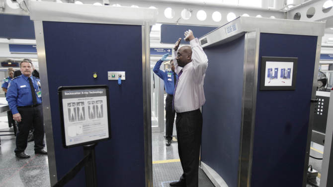 FILE - In this Monday, March 10, 2010 file photo, volunteers pass through the first full body scanner, which uses backscatter technology, installed at O'Hare International Airport in Chicago. Those airport scanners with their all-too revealing body images will soon be going away. The Transportation Security Administration says the X-ray scanners will be gone by June 2013 because the company that makes them can't fix the privacy issues. The other airport body scanners, which produce a generic outline instead of a naked image, are staying. (AP Photo/M. Spencer Green, File)