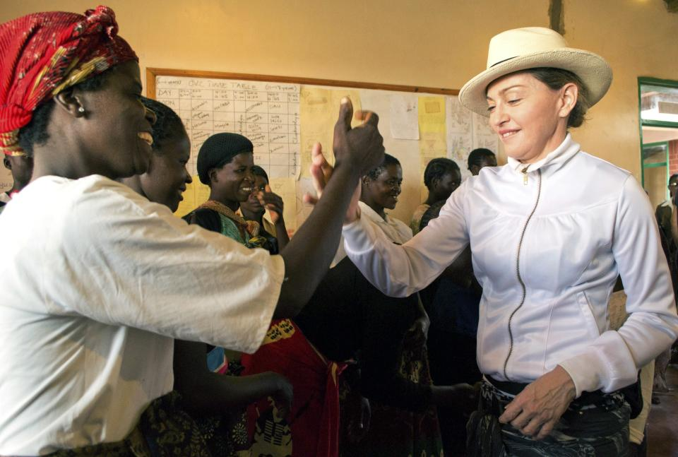 US performer Madonna greets volunteers at the Mphandura orpahange near Lilongwe, Malawi Friday April 5, 2013.  Madonna, is spending her fourth day in the southern African country from where she adopted two children. (AP Photo/Thoko Chikondi)