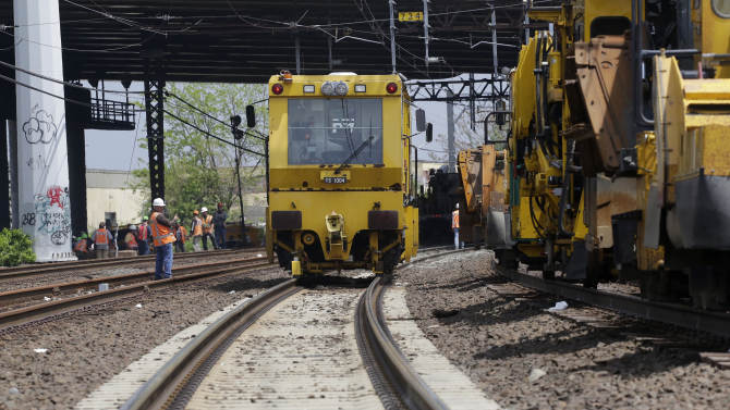 Metro North railroad employees use heavy equipment to repair tracks near Bridgeport, Conn., Monday, May 20, 2013. A train collision on Friday injured 72 people and disrupted rail service into New York City. (AP Photo/Mark Lennihan)