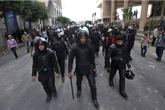 Egyptian riot police march during clashes with protesters, not seen, near Tahrir Square in Cairo, Egypt,Wednesday, Jan. 30, 2013. Egypt's liberal opposition leader called for a broad national dialogue
