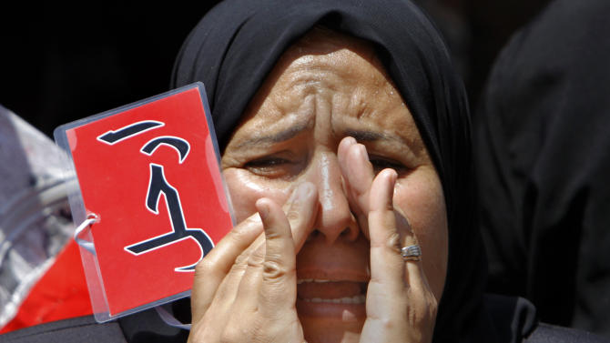 """An Egyptian protester shouts anti-President Mohammed Morsi slogans and holds a red card with Arabic reading """"leave"""", during a protest in Tahrir Square, the focal point of Egyptian uprising, in Cairo, Egypt, Friday, June 28, 2013. Elsewhere, thousands of supporters of Egypt's embattled president are rallying in the nation's capital in a show of support ahead of what are expected to be massive opposition-led protests on June 30 to demand Mohammed Morsi's ouster.(AP Photo/Amr Nabil)"""