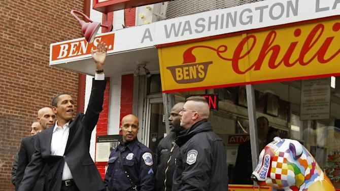 FILE - In this Jan. 10, 2009 file photo, then-President-elect Barack Obama waves to onlookers as he leaves Ben's Chili Bowl in Washington where he stopped to eat with then-Washington Mayor Adrian Fenty, second from left. Call it the Obama effect: a presidential visit can be good advertising for the restaurants and businesses. Interest in where and what Obama and his family does can be explained with one word: authenticity. (AP Photo/Gerald Herbert, File)