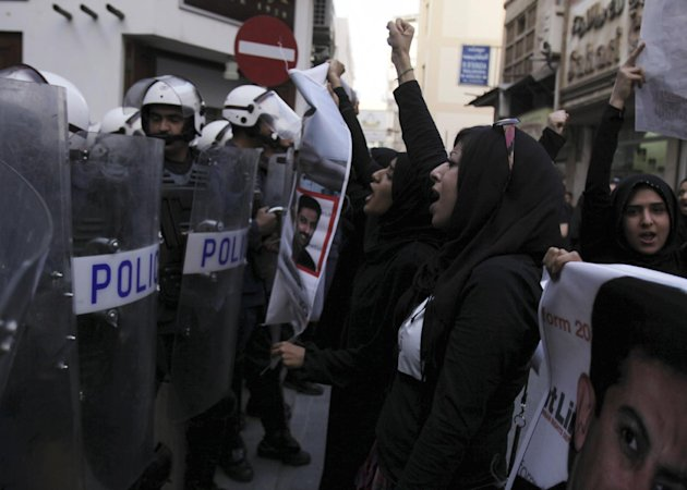 Bahraini anti-government activist Zainab al-Khawaja, second right, gestures and chants slogans in front of riot police during a protest Wednesday, April 18, 2012, in downtown Manama, Bahrain. Security forces fired stun grenades at the protesters who swarmed into a cultural exhibition for the Formula Bahrain One Grand Prix race, setting off street battles and sending visitors fleeing for cover. (AP Photo/Hasan Jamali)