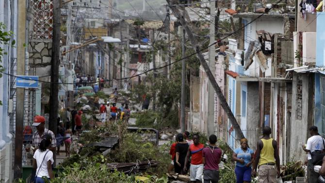 In this Oct. 26, 2012 photo, residents walk past tree branches and power lines felled by Hurricane Sandy in Santiago de Cuba. Residents of Cuba's second city continued to find themselves without power or running water, Monday, Oct. 29, 2012, four days after Hurricane Sandy hit. (AP Photo/Franklin Reyes)