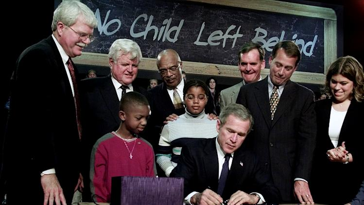 FILE - In this Jan. 8, 2002, file photo President George W. Bush, seated, signs into law a sweeping federal education bill, No Child Left Behind, at Hamilton High School in Hamilton, Ohio. Cast as a symbol of possibility, the law offered the promise of improved schools for the nation's poor and minority children and better prepared students in a competitive world. Yet after a decade on the books, Bush's most hyped domestic accomplishment has become a symbol to many of federal overreach and Congress' inability to fix something that's clearly flawed. In the image from left are Rep. George Miller, D-Calif., Sen. Edward Kennedy, D-Mass., Education Secretary Rod Paige, Sen. Judd Gregg, R-N.H., Rep. John Boehner, R-Ohio, woman at right unidentified. Children with Bush are Tez Taylor, left, and Cecilia Pallcio, right. (AP Photo/Ron Edmonds, File)