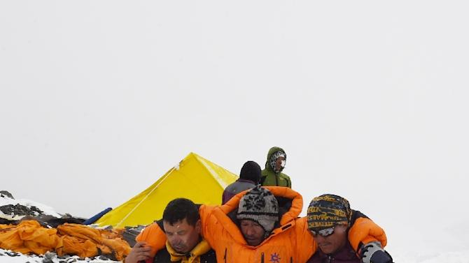 In this photograph taken on April 25, 2015, rescuers assist an injured person after an earthquake triggered by an avalanche flattened parts of Everest Base Camp