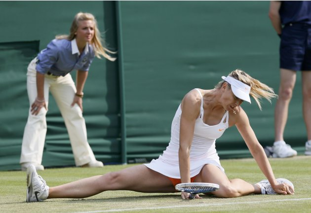 Maria Sharapova of Russia slips during her women's singles tennis match against Michelle Larcher De Brito of Portugal at the Wimbledon Tennis Championships, in London