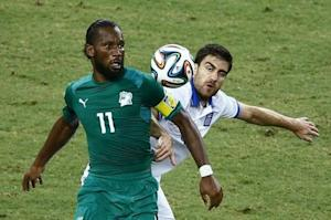 Ivory Coast's Drogba fights for the ball with Greece's Papastathopoulos during their 2014 World Cup Group C soccer match in Fortaleza
