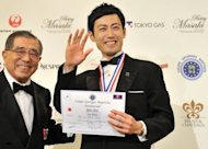 Shin Miyazaki of Japan (R) stands next to Hisanori Isomura (L), president of committee for the competition, as he celebrates his win during an awards ceremony of the International Georges Baptiste Cup world service competition in Tokyo
