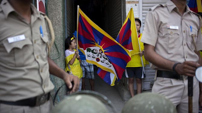 Exile Tibetans carry their national flags as Indian policemen stand to stop them from marching to Jantar Mantar during a protest to highlight Chinese control over Tibet, coinciding with the visit of  Chinese President Xi Jinping in New Delhi, India, Wednesday, Sept. 17, 2014. Xi was traveling Wednesday to India, where he and Prime Minister Narendra Modi are expected to discuss trade, infrastructure and territorial disputes. (AP Photo/Tsering Topgyal)