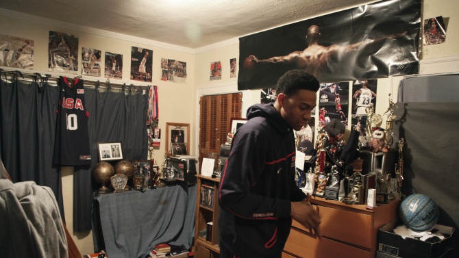 """In this photo taken in Chicago, on Monday, March 12, 2012, Jabari Parker walks around his bedroom preparing to go to a 6:00 a.m. Bible study  in Chicago's Hyde Park neighborhood before school. There's a reminder to """"put the Lord first"""" on Jabari's bedroom door along with several sheets of eight-by-10 white paper. One lists the Ten Commandments. Then, there's his """"Always Remember"""" list, with his own personal rules that reflect helping and caring for others. (AP Photo/Charles Rex Arbogast)"""