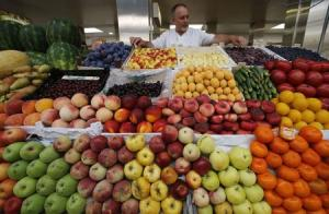 A vendor sells vegetables and fruits at the city market in St.Petersburg