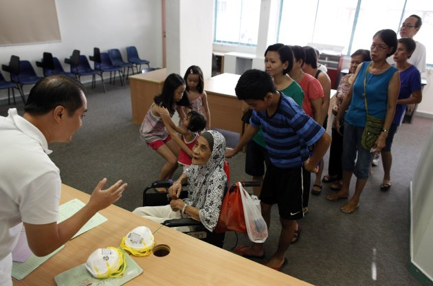 """People queue up for free N95 masks at a distribution centre in Singapore June 23, 2013. One million N95 masks will be given to the poorest 200,000 households for free by the government starting from Sunday, according to authorities. The """"haze"""" caused by fires in Riau province on Indonesia's Sumatra island has shrouded neighbouring Singapore but air quality in the city state improved over the weekend after reaching hazardous levels. REUTERS/Edgar Su (SINGAPORE - Tags: ENVIRONMENT HEALTH)"""