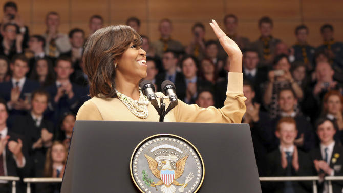US First Lady Michelle Obama waves after her husband US President Barack Obama delivered a keynote address ahead of the G-8 summit at Waterfront Hall in Belfast, Northern Ireland on Monday, June 17, 2013. (AP Photo/ Paul Faith, Pool)